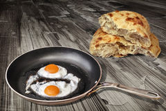 Pair Of Sunny Side Up Eggs Fried In Old Frying Pan Set On Weathered Cracked Garden Table With Pitta Bread Loaf Torn Halves Stock Photography