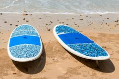 Pair of surfboards lie on a sandy beach. Near the sea Royalty Free Stock Images