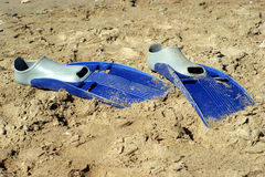 Pair of swimfins on the sand at sea Stock Image