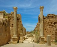 A pair of tall columns against stone walls under a blue sky at ancient Roman ruins of Leptis Magna in Libya. Two tall marble columns with high stone wall under royalty free stock photos