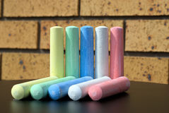 Pair of ten chalks of five different colors on table. stock photography
