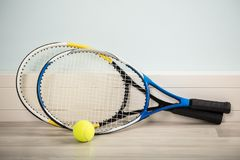 Pair Of Rackets And A Ball. Pair Of Tennis Rackets And A Ball On A Hardwood Floor Royalty Free Stock Images