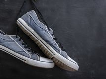 Pair of textile blue sneakers hang on a string. On a black background, copy space stock images