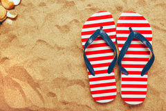 Pair of thongs or flip flops on beach sand. Top view of summer holiday vacation accessories on sandy summertime resort coastline Royalty Free Stock Photo
