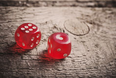 Pair of thrown red dices on  wooden table Royalty Free Stock Photo