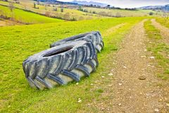 Pair of tires of a big tractor dismantled and left in a Italian. Country road Stock Photo