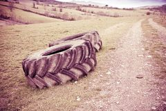 Pair of tires of a big tractor dismantled and left in a Italian. Country road - toned image Stock Images
