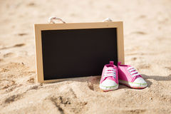 Pair of toddler shoes and mini chalk board on the sand Royalty Free Stock Image