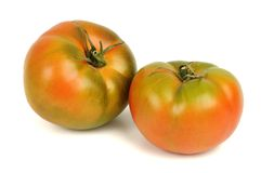 Pair of tomatoes over white. Pair of green tomatoes isolated over white Royalty Free Stock Images