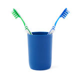 Pair of toothbrushes in blue plastic cup isolated over white background. Pair of green and blue toothbrushes in blue plastic cup isolated over white background Stock Photos