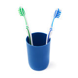 Pair of toothbrushes in blue plastic cup isolated over white background. Pair of green and blue toothbrushes in blue plastic cup isolated over white background Royalty Free Stock Photos