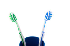 Pair of toothbrushes in blue plastic cup isolated over white background. Pair of green and blue toothbrushes in blue plastic cup isolated over white background Stock Photo