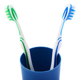Pair of toothbrushes in blue plastic cup isolated over white background. Pair of green and blue toothbrushes in blue plastic cup isolated over white background Royalty Free Stock Images