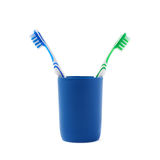 Pair of toothbrushes in blue plastic cup isolated over white background. Pair of green and blue toothbrushes in blue plastic cup isolated over white background Stock Image