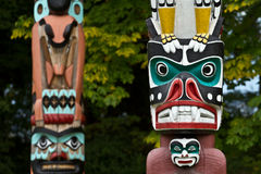 A Pair of Totem Poles. Close up of two totem poles in Stanley Park, Vancouver, British Columbia Royalty Free Stock Image