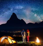 Pair tourists holding hands, standing near camp and enjoying beautiful starry sky and Milky way. Astrophotography Royalty Free Stock Images