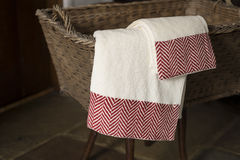 Pair of Towels Hanging From Basket on Wooden Stool stock photos