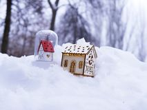 A pair of toy decorative houses with lighted illumination on the snow. The concept of winter seasonal holidays, Christmas, a new house in the new year, home stock images