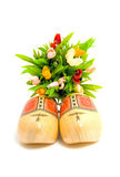 Pair of traditional Dutch yellow wooden shoes. With little tulips over white background Stock Image