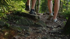 A pair of travelers walk along a narrow mountain path in the forest. In the frame, only the legs are visible, the rear. View. Adventure and active lifestyle stock footage