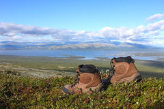 A pair of trekking boots on the edge, other mountains and lake i Stock Image