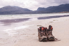 Pair of trekking boots on a remote beach with sea and mountains Stock Image