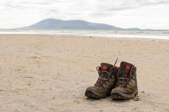 Pair of trekking boots on a remote beach with sea and mountains Stock Photo
