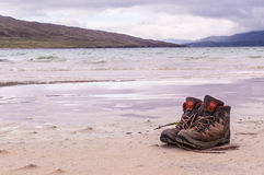 Pair of trekking boots on a remote beach with sea and mountains Royalty Free Stock Photos