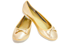 Pair of trendy ballet flats in golden leather on white background. Royalty Free Stock Photo