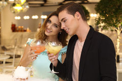 A pair of trendy lovers having dinner in fusion restaurant. A pair of trendy lovers having Smokey drinking in fusion restaurant men black jacket suit women in royalty free stock photos