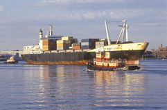 A pair of tug boats working together to turn around a ship loaded with cargo for international destinations from Boston, Massachus Royalty Free Stock Photography