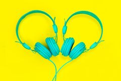 A pair of turquoise headphones in the shape of a heart on a yellow background. Summer love music festival royalty free stock photography