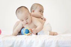A pair of twinborn babies. A pair of Chinese twinborn babies are in bed and playing with toys Stock Photography