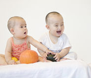 A pair of twinborn babies. A pair of Chinese twinborn babies are playing with pumpkin very happily Royalty Free Stock Photography