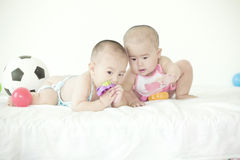 A pair of twinborn babies. A pair of lovely twinborn babies is playing toys in bed Stock Photography