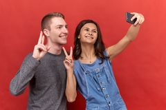 Pair two friends doing a selfie on phone, smiling and looking happily into camera on isolated background. stock photo