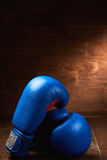 Pair of the two red boxing gloves lie on wooden table against wooden background. Stock Photography