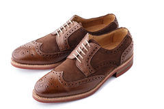Pair of two tone men brogues. Unworn, laced pair of handcrafted shiny, two tone men brogues (also known as derbys, gibsons or wingtips) on durable welted red Royalty Free Stock Photo
