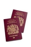 A pair of UK British passports. Two UK British passports for United Kingdom of Great Britain and Northern Ireland,  on white with path Stock Photo