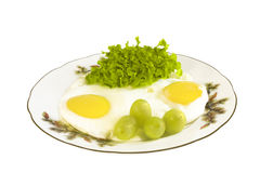 Pair up. Fried eggs on a plate with green salad and grapes Stock Photos