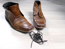 Pair of used shoes with shoelaces. Out and in front of them in a clew Royalty Free Stock Photos