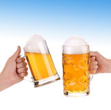 Pair of very cool beer glasses on a blue sky. Royalty Free Stock Photo