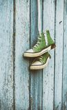 Pair of very old green classic sneakers hanging on white lace. Vintage toning stock images