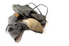 Pair of very old women`s cloth and leather shoes with extensive wear, on white stock photo