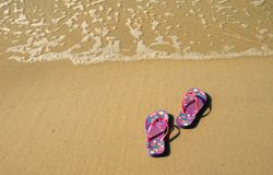 Pair of vibrant colored flip-flops or sandals on golden sand beach with the wave swash. Background Royalty Free Stock Photography