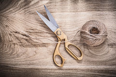 Pair of vintage golden scissors rope on wooden board Stock Photography