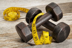 Iron dumbbells and measuring tape Royalty Free Stock Photos