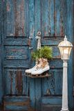 Pair of vintage white Ice Skates with Christmas decoration hanging on the blue rustic door and a big lantern. Toned stock image