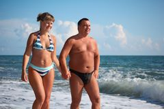 Pair walk in sea surf Stock Images