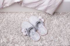 Pair of warm female slippers on furry carpet. Fur slippers on a fluffy carpet near the bed royalty free stock photos